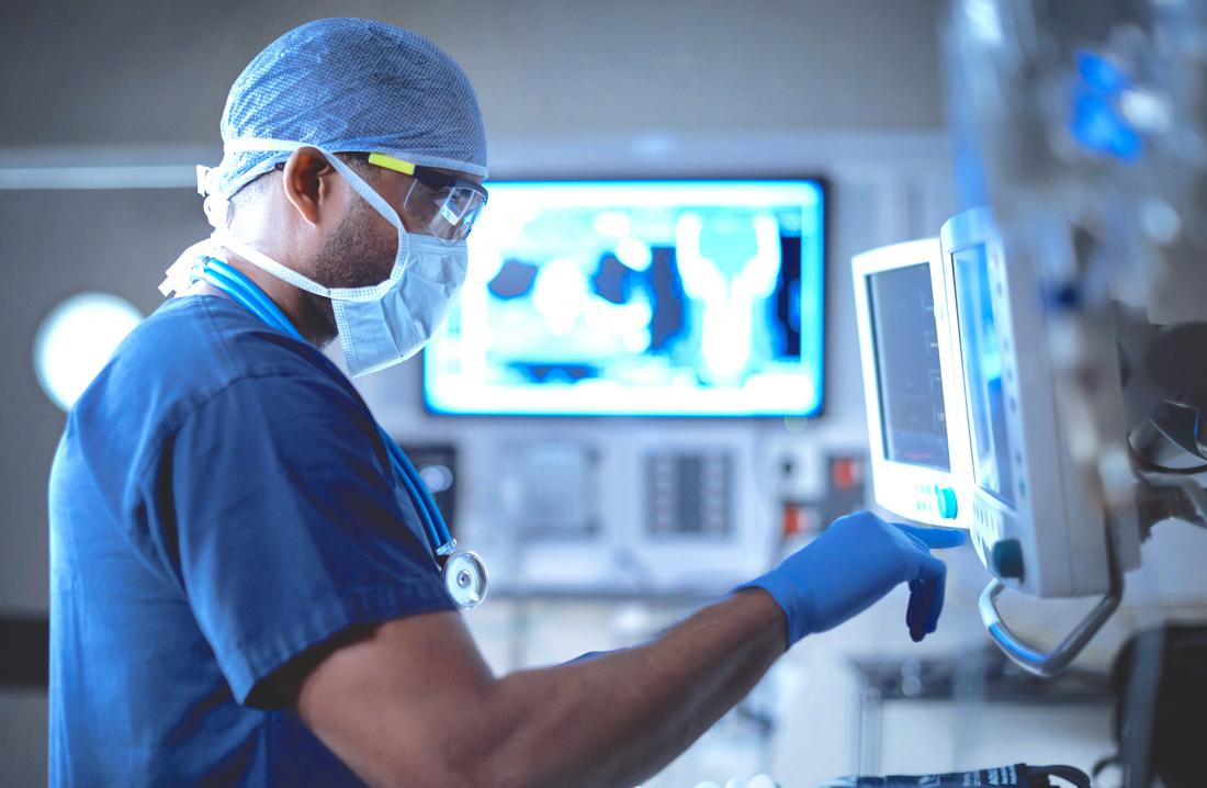 Surgeon preparing for bone graft in operating theatre touching monitor.