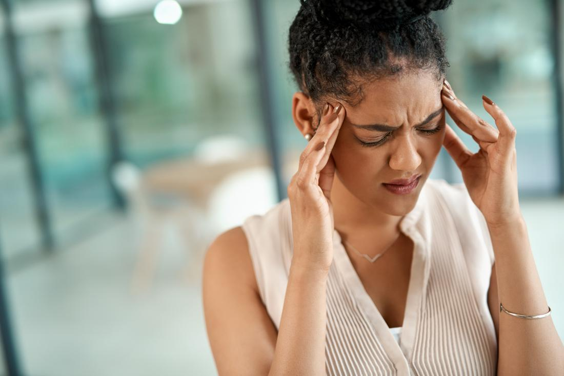 Woman with headache massaging temples.