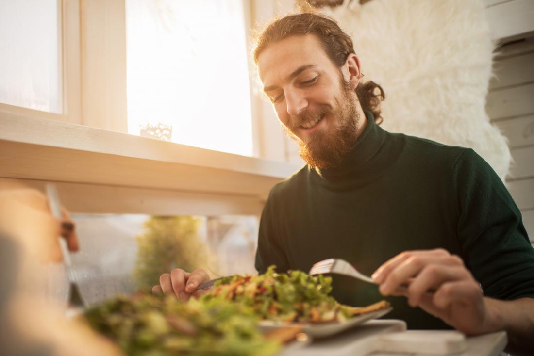 Man eating salad smiling at healthy meal