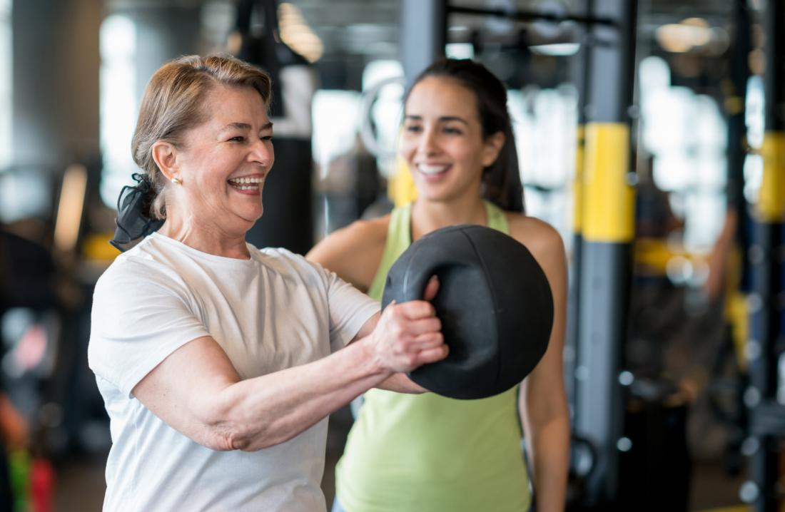 Middle-aged woman doing weight lifting in gym with personal trainer