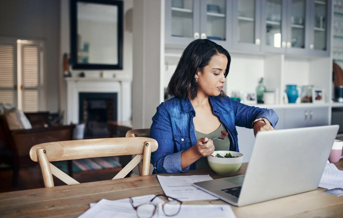 Woman eating food at table in front of laptop, looking at her watch
