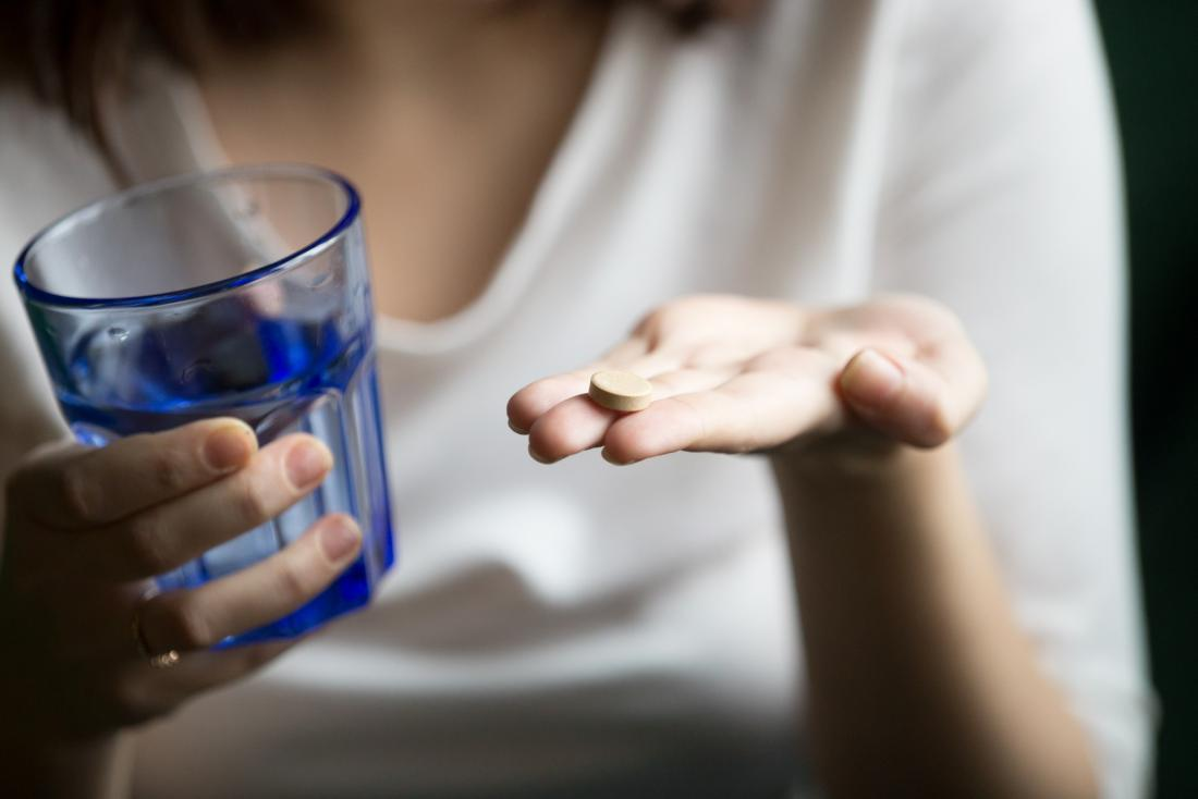 person holding antidepressant and a glass of water