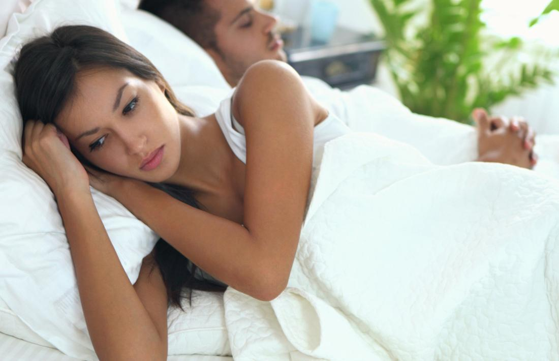Woman in bed looking anxious due to Bartholins abscesses