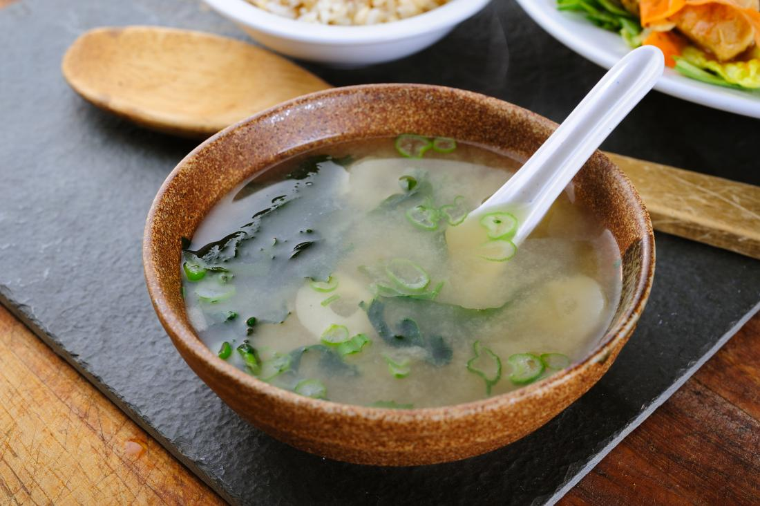 Miso soup in bowl with leek and seaweed.