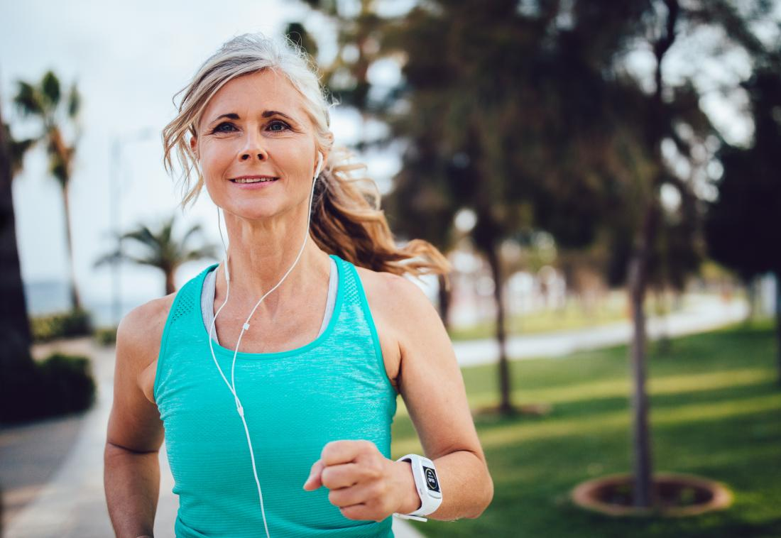 Woman jogging through park listening to headphones.