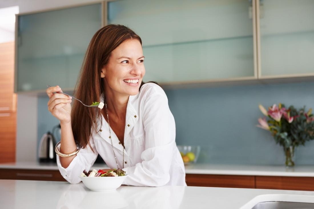 Smiling happy woman eating food in kitchen.