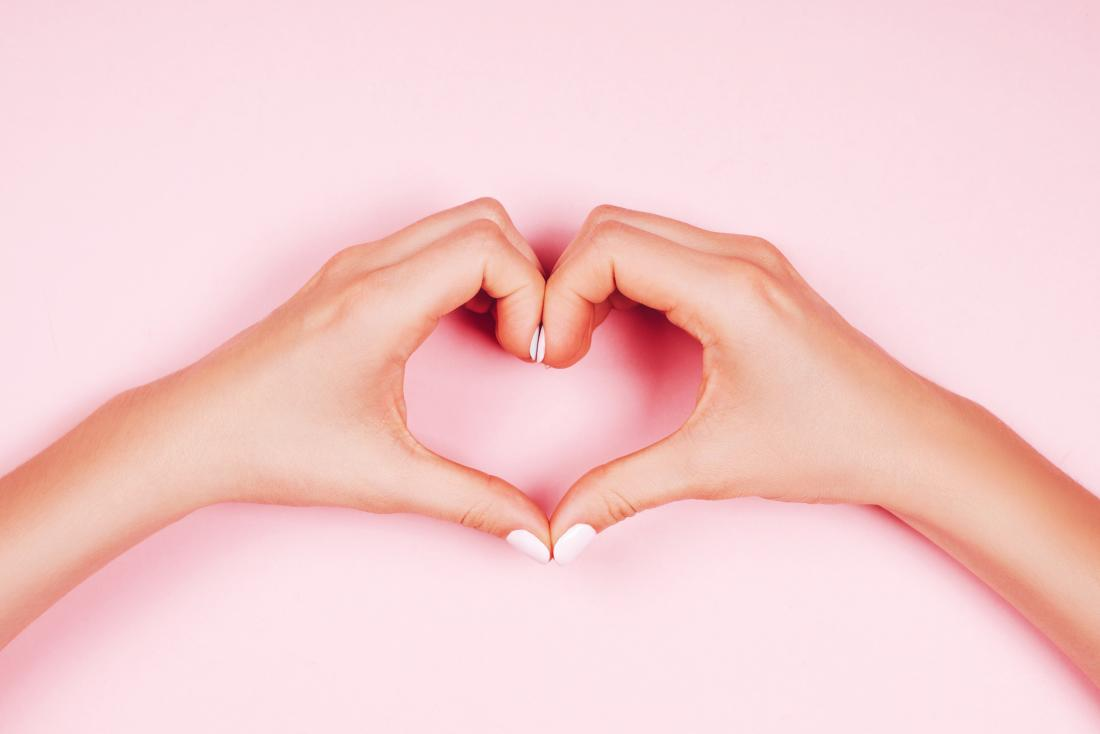 woman making heart sign with her hands on pick background