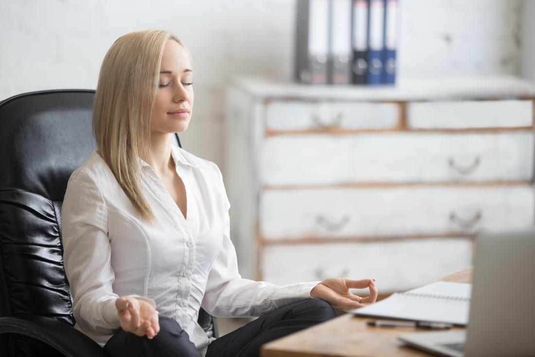 woman deep breathing and meditating at work