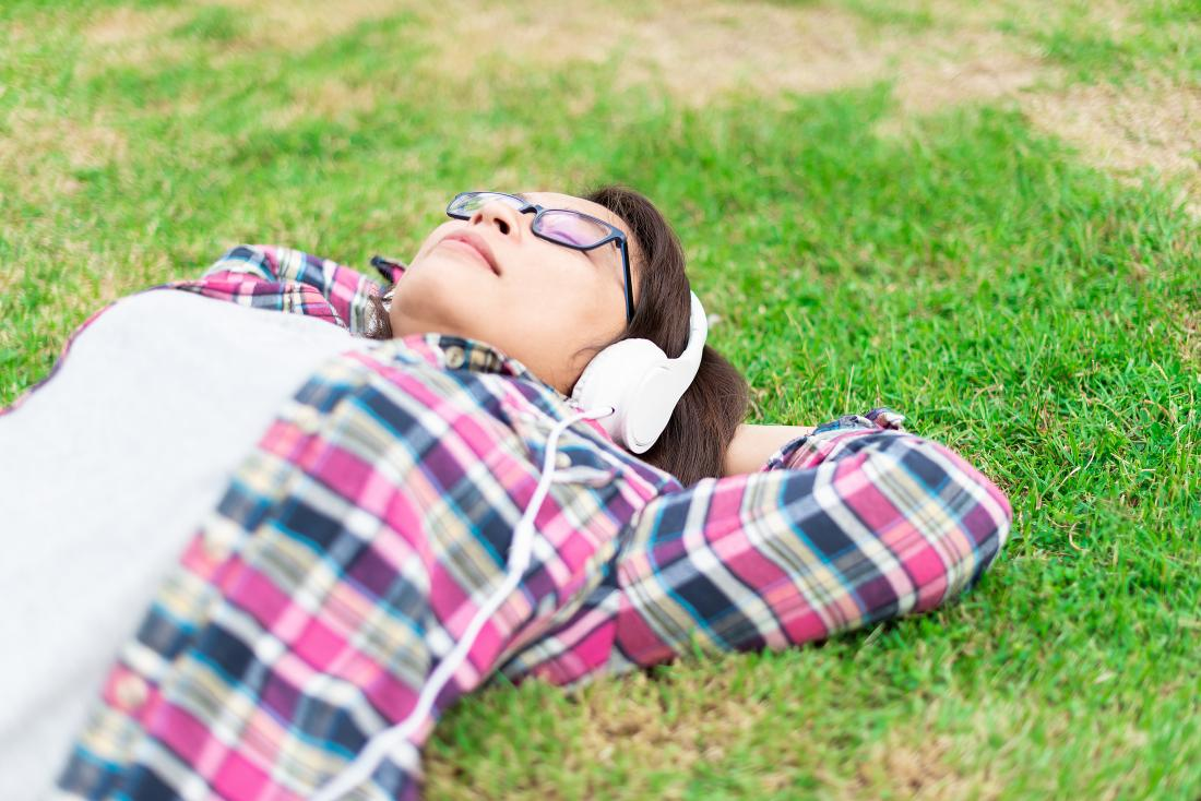 Woman relaxing laying down on grass outdoors listening to music through headphones