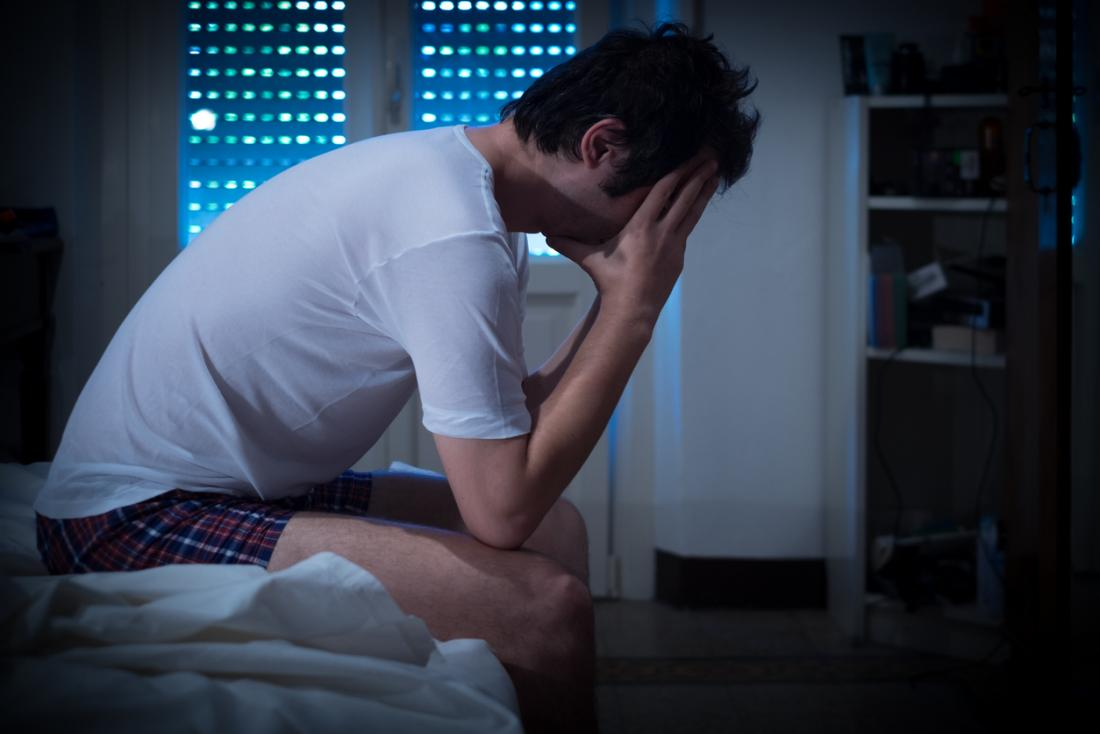 Man sitting on edge of bed with insomnia