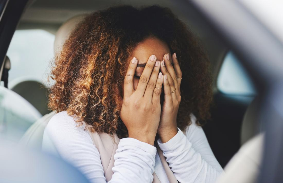 Stressed and anxious woman with hands covering face sitting in car.