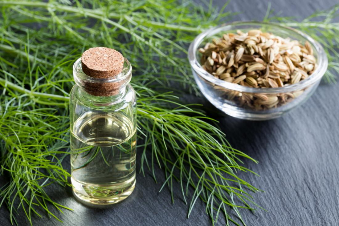 Fennel seeds in bowl next to leaf and bottle of essential oil