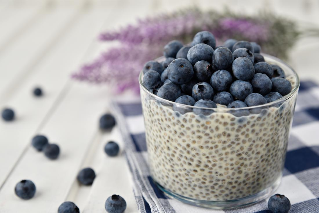 Chia seeds in yoghurt pot topped with blueberries.