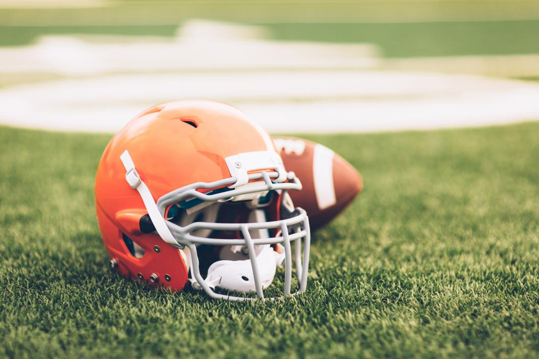 Football helmet and ball on grass or turf.