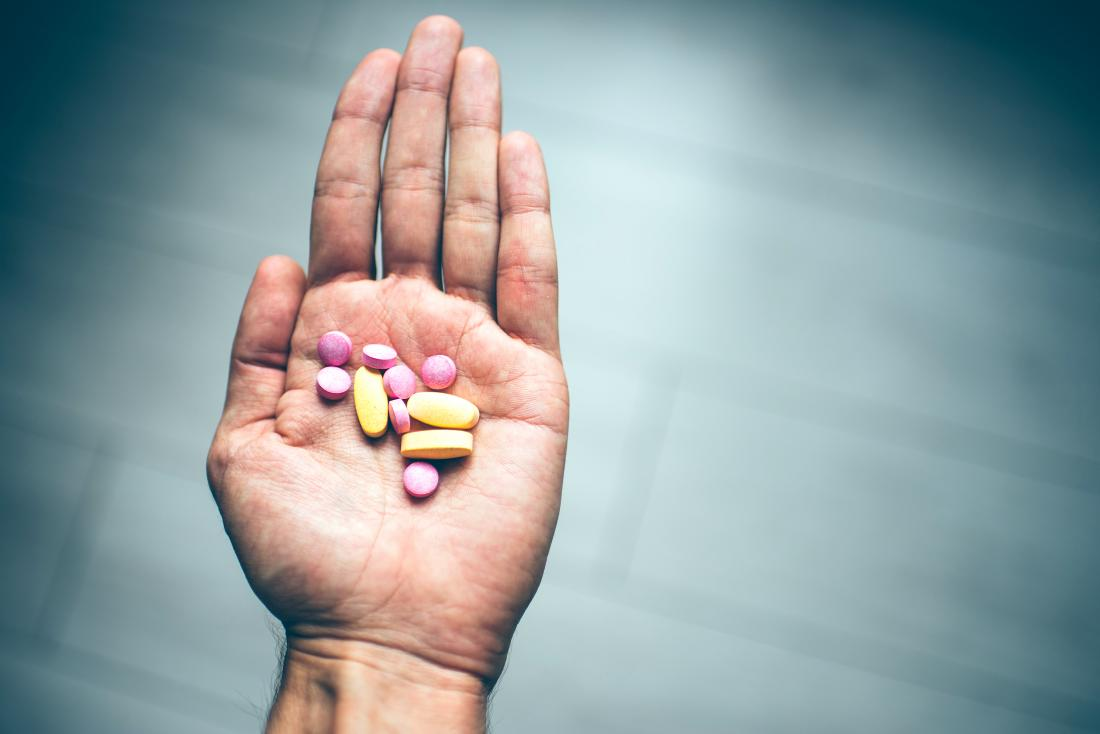 Person holding vitamin and mineral supplements in their hand
