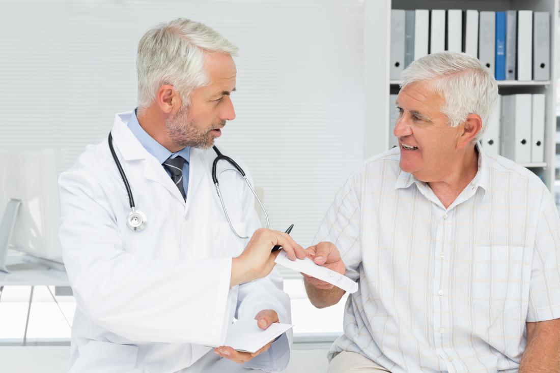 doctor handing male patient a prescription