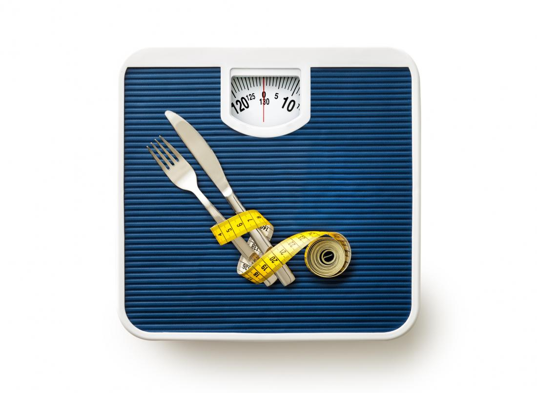 scales with measuring tape and cutlery