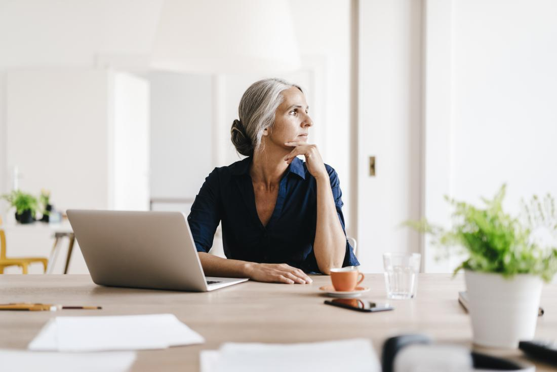 Mature post-menopausal woman sitting in office.