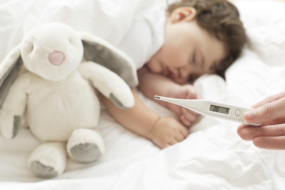 Toddler asleep with a temperature monitor in foreground showing fever.