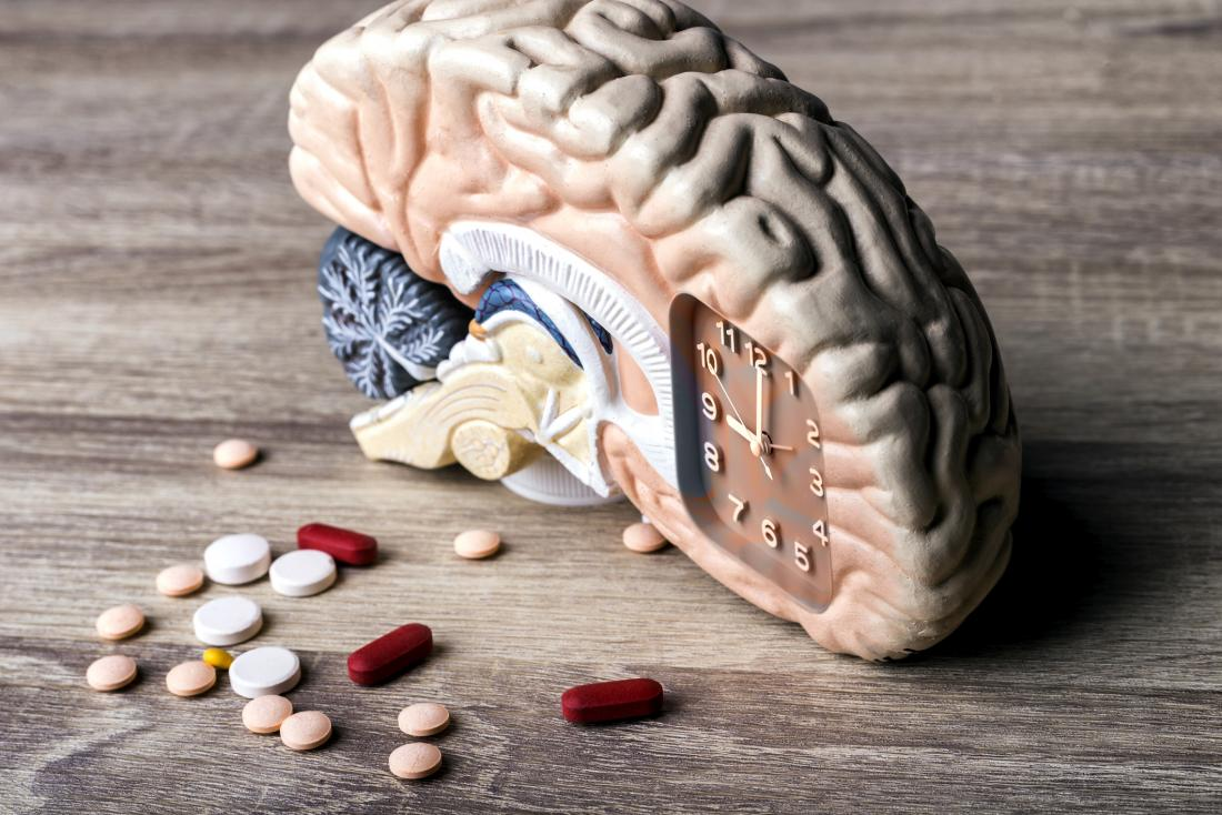 brain with a clock and pills
