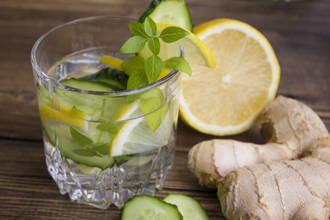 Glass of water with ginger, lemon, and herbs.