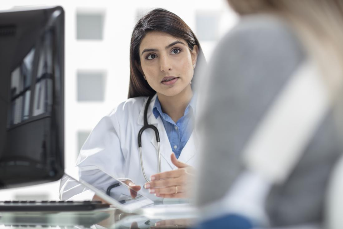 A doctor at a desk showing tablet to patient