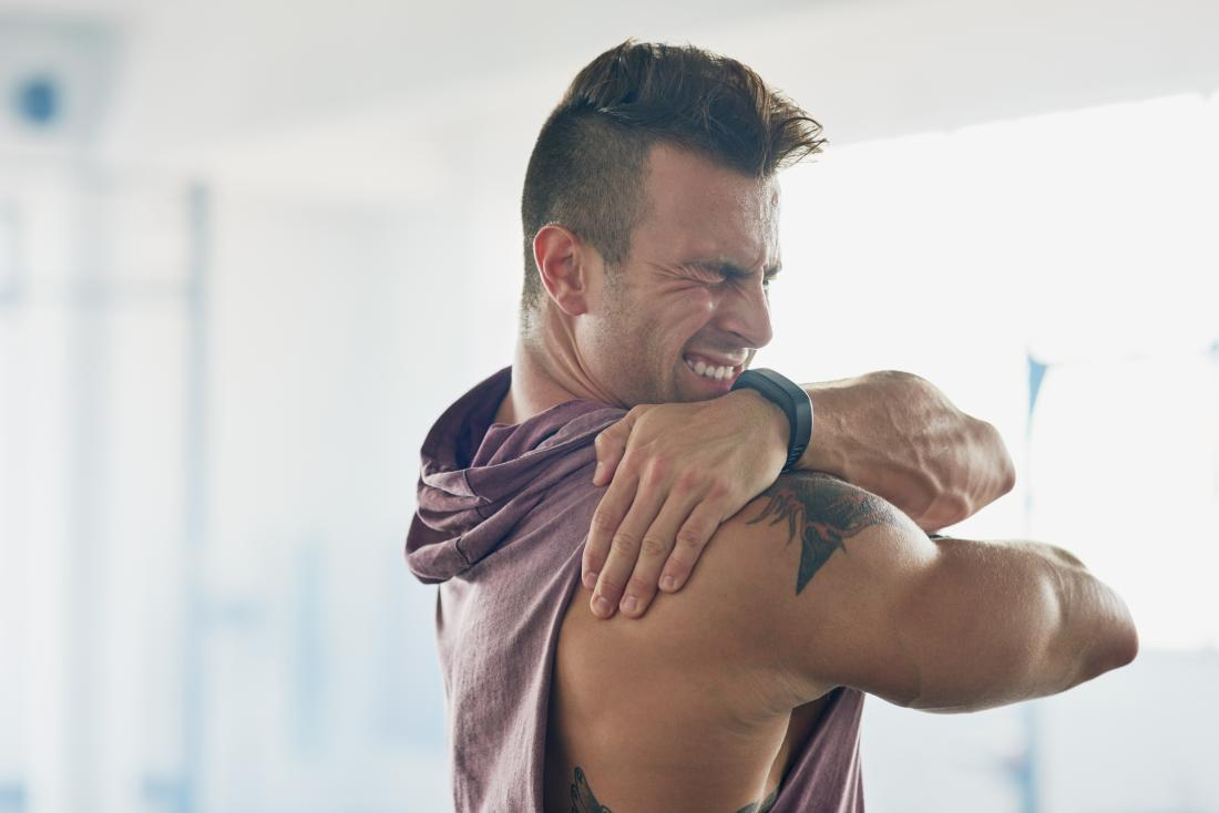 Man with painful shoulder holding it and grimacing.