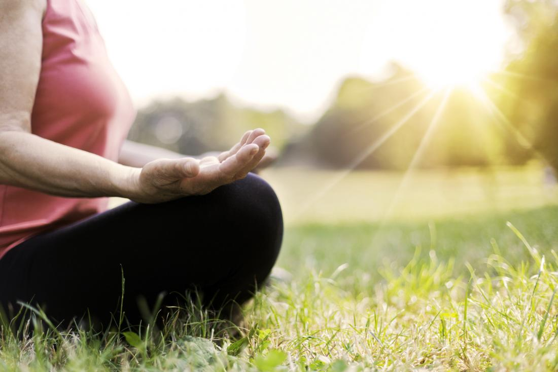 Woman meditating which can help with stress that causes RA flares