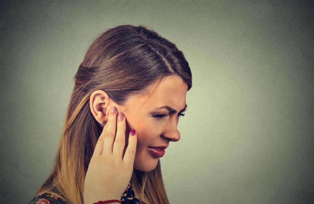 Woman holding ear due to chronic ear infection
