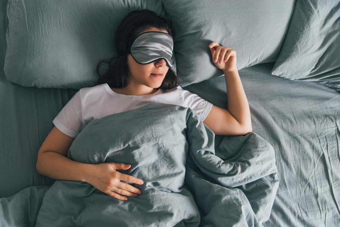 Person sleeping in bed with eye mask on.