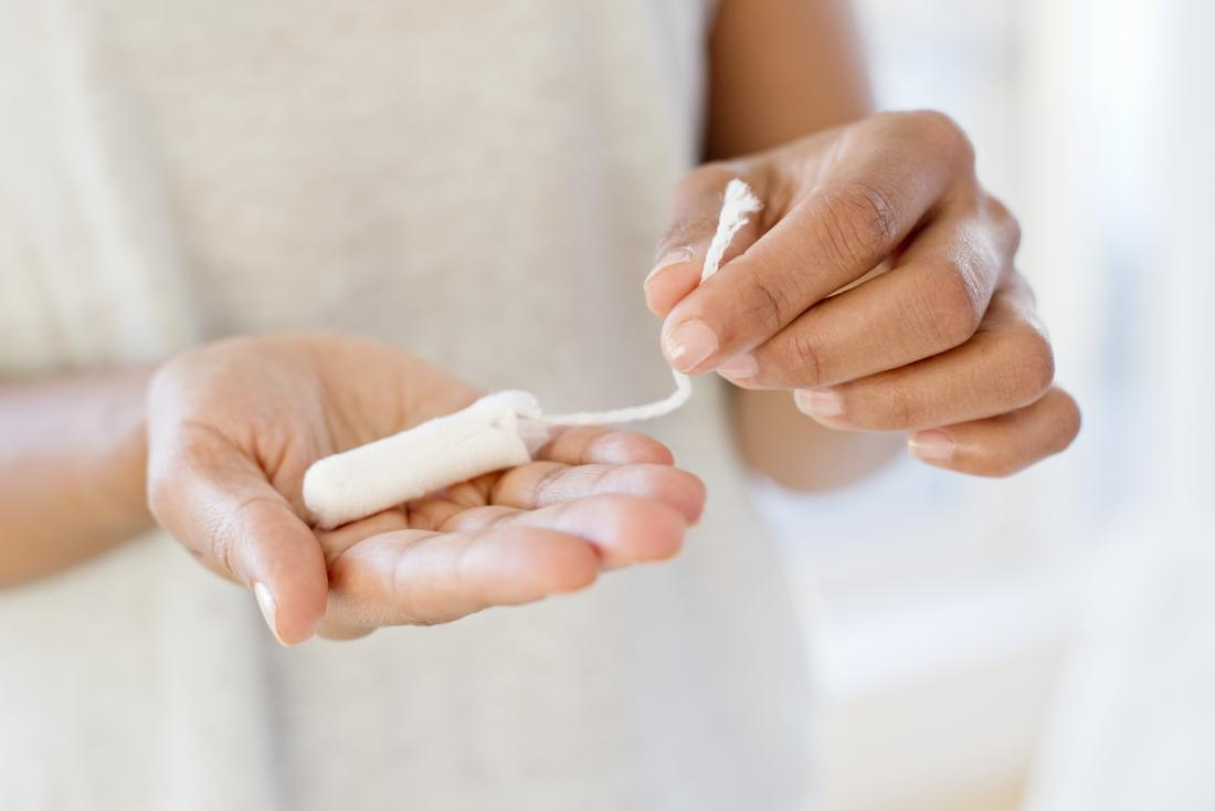 Woman with tampon in hand hoping to stop periods after they have started