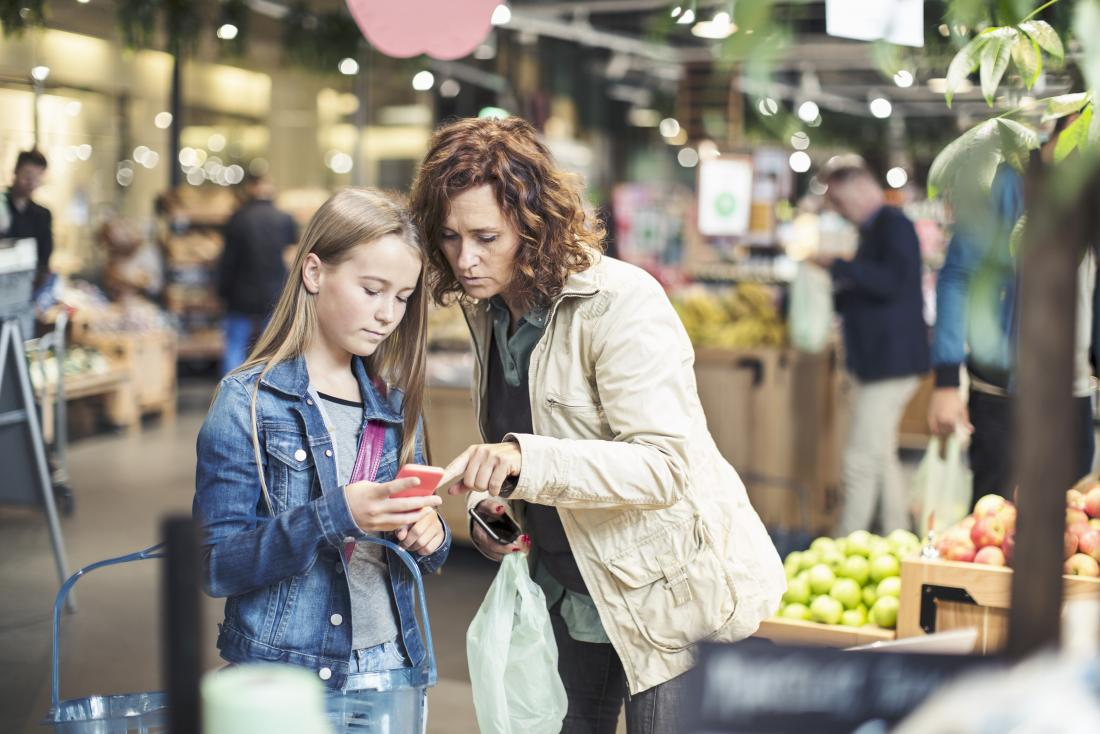 Mother and daughter in supermarket looking at phone