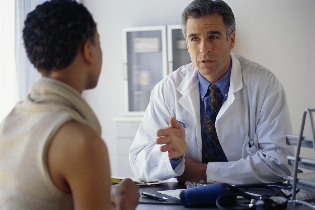 يشرح الطبيب شيئًا للمريض عبر المكتب.