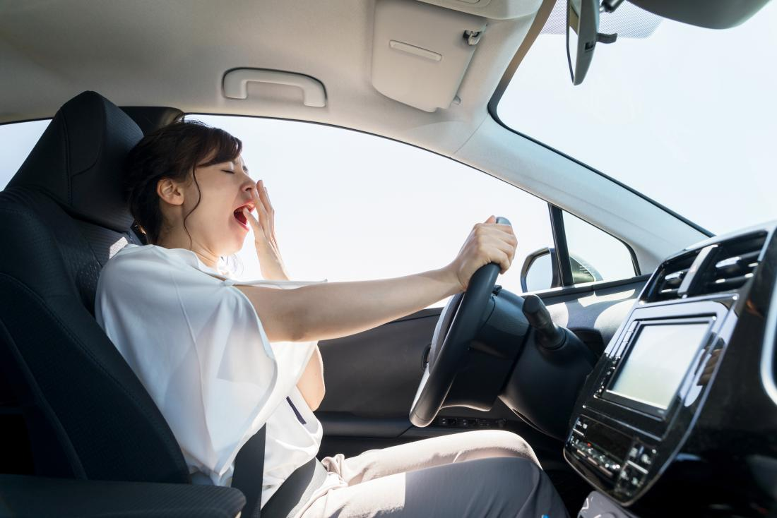 Yawning woman in a car who may be stressed