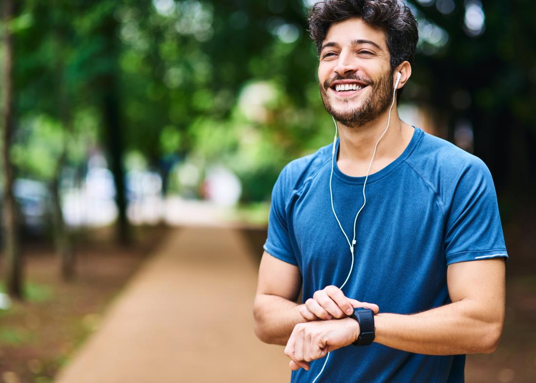Man outdoors running and jogging smiling and listening to ipod