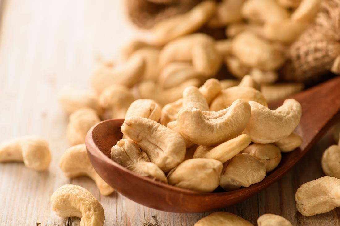 Cashew nuts on wooden spoon.