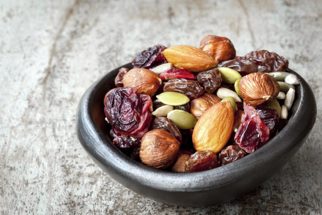 Trail mix in small bowl, with cranberries, almonds, seeds, and hazelnuts.