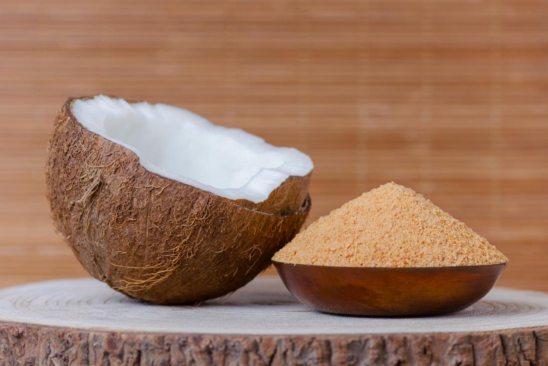 Coconut next to coconut sugar in bowl on tree stump.