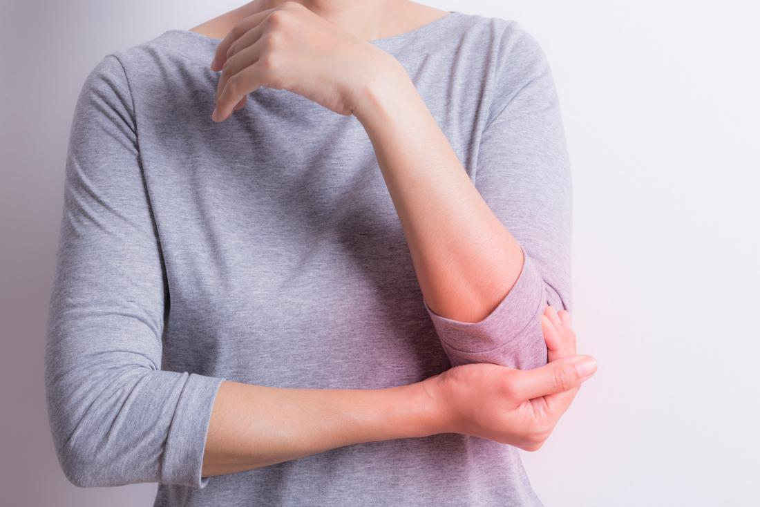 Woman holding her elbow in pain, possibly due to lupus and arthritis.