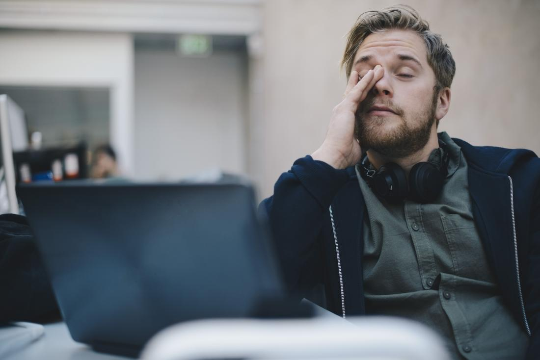Tired or fatigued man rubbing eyes during stressful day at work