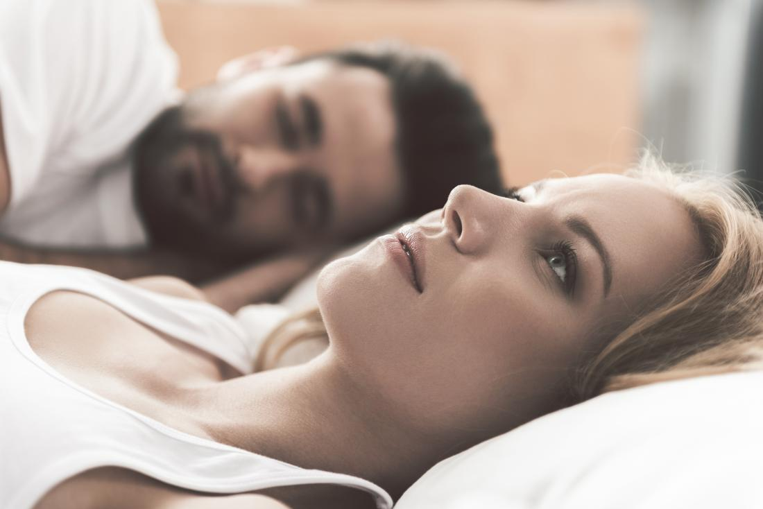 woman awake in bed next to partner worrying about sex after hysterectomy