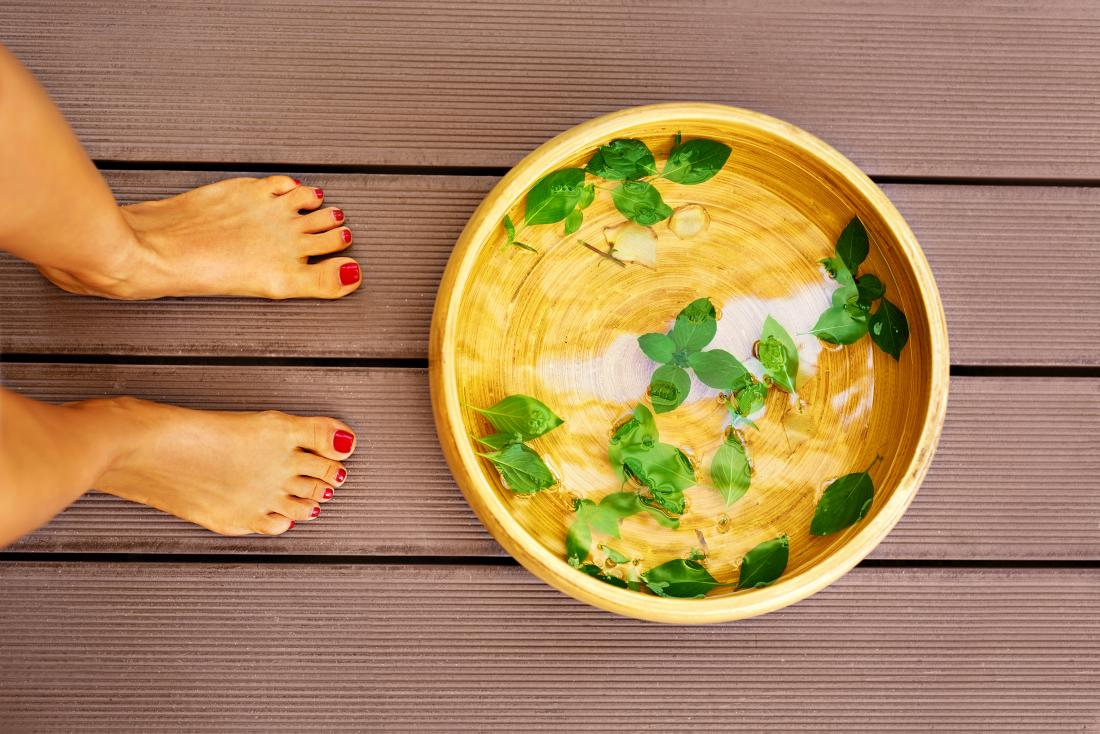 Woman next to bowl with soak for foot detox