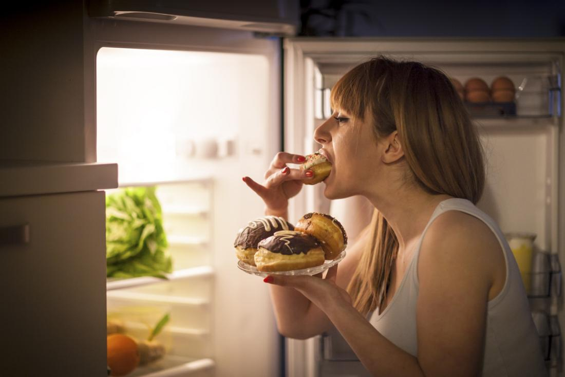 woman raiding the fridge for cream cakes