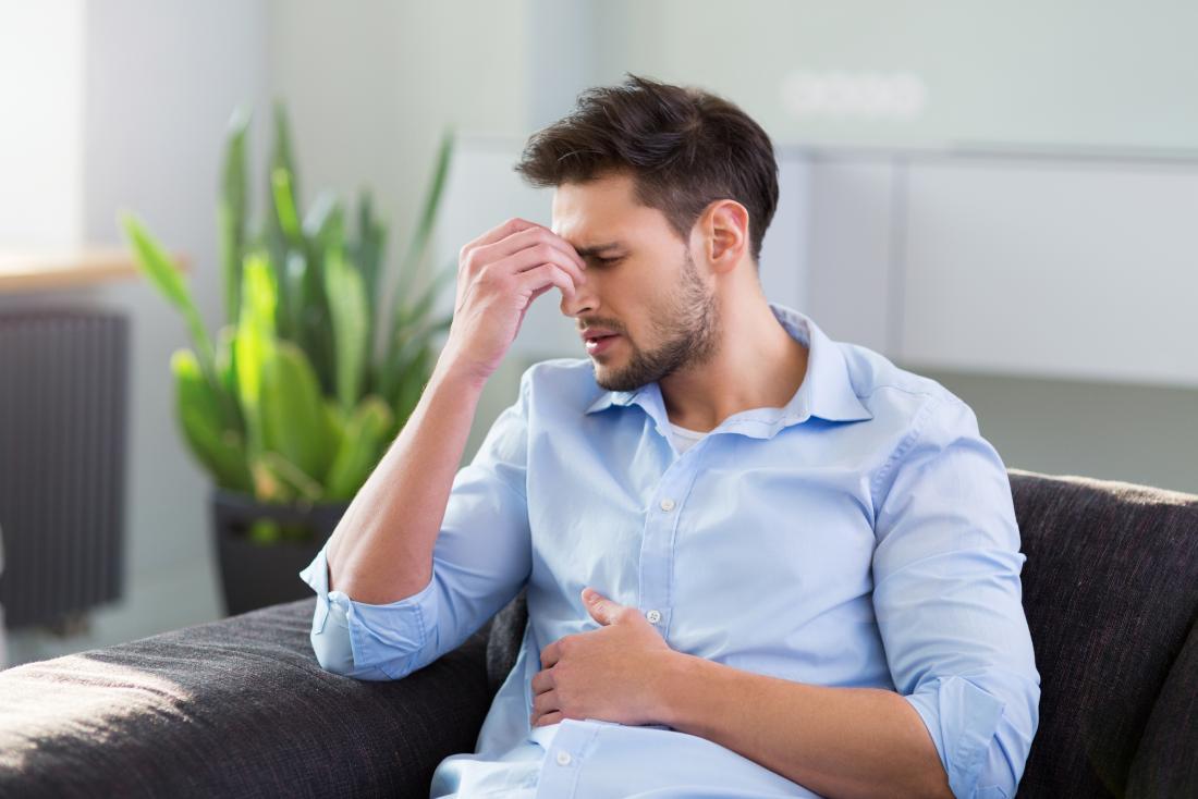 man with headache sitting on settee
