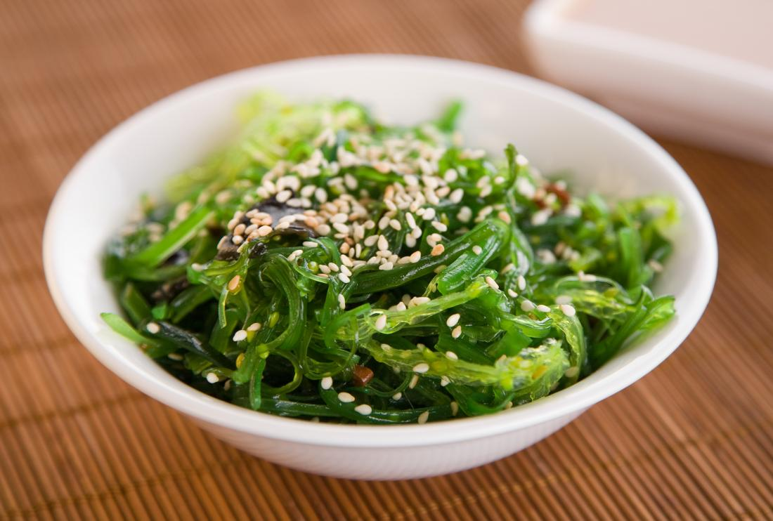 Nori seaweed in a bowl with seeds on top.