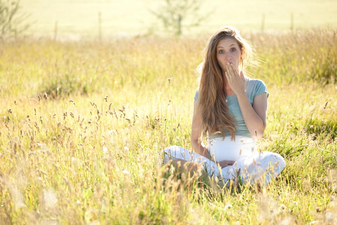 pregnant woman sitting in a meadow with hand up to her mouth