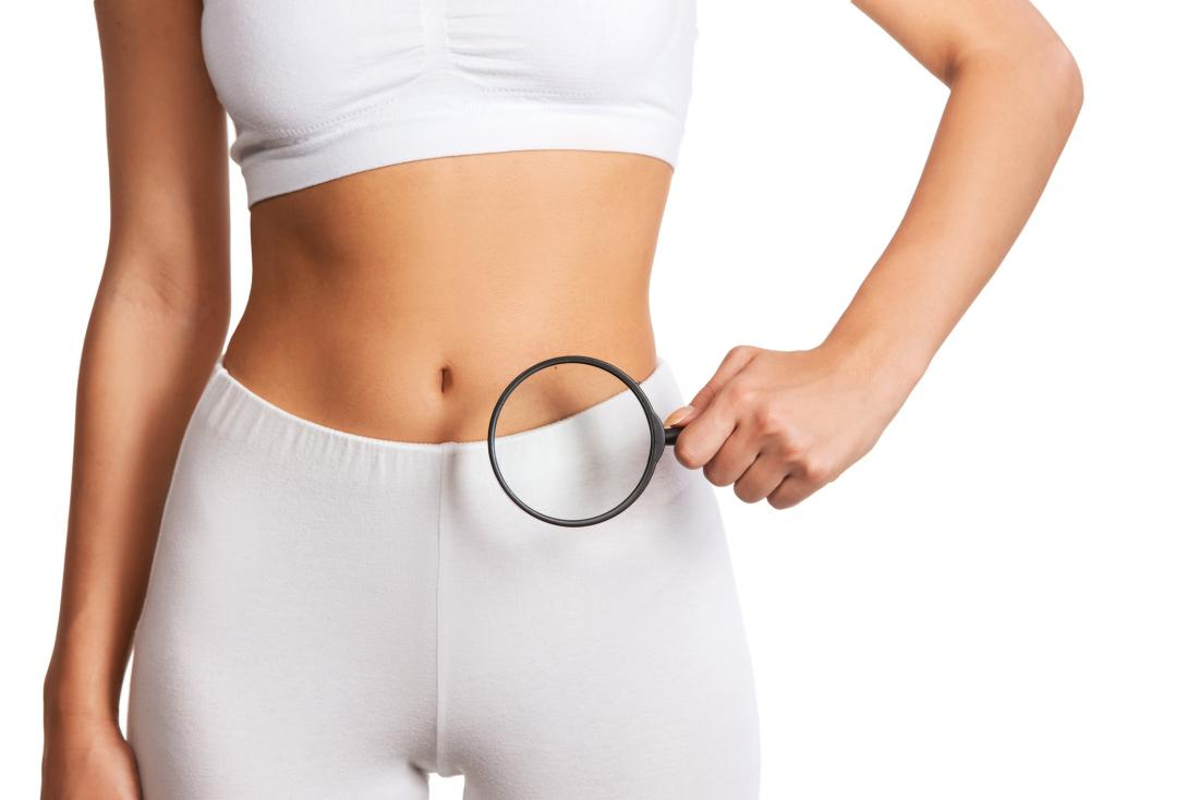 woman holding magnifying glass over abdomen