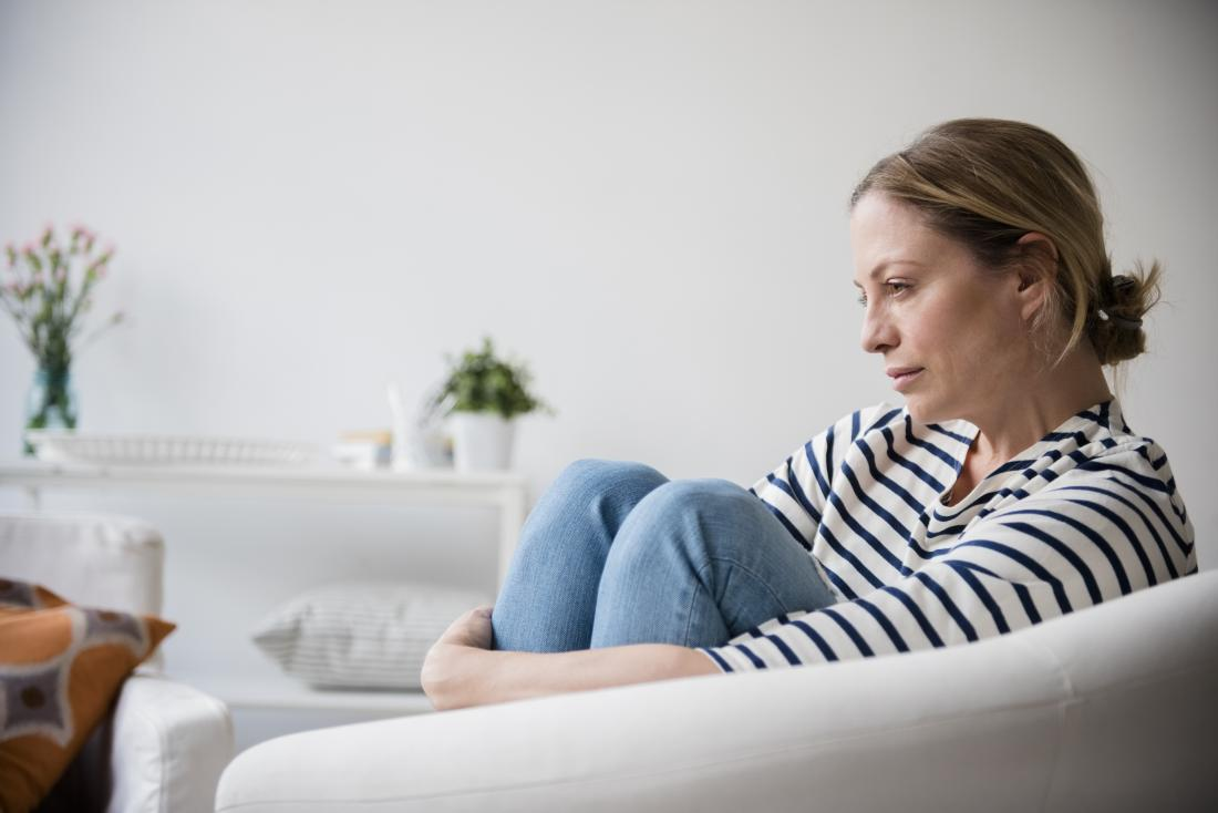 Sad and worried woman holding legs while sitting on armchair