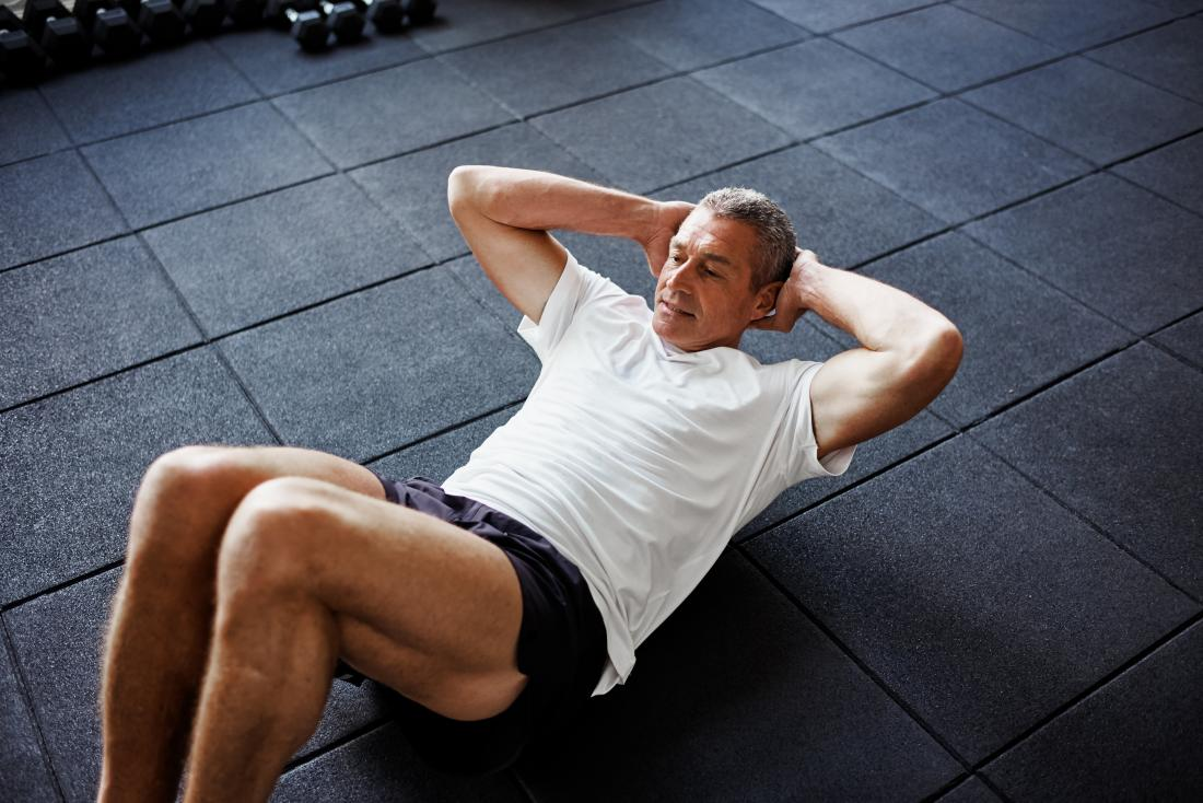 Man doing partial curls or sit ups on floor.