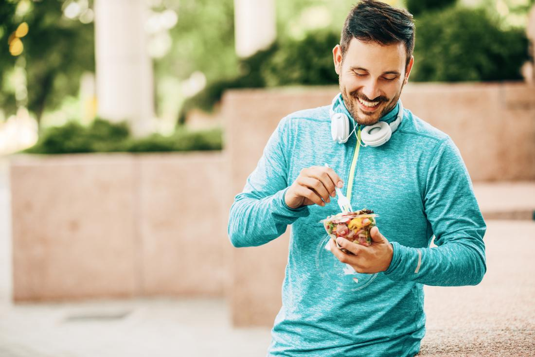 Man in running gear outdoors eating from takeaway pot of pasta.